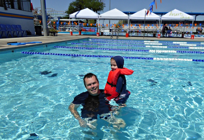 Man and child wearing life vest in a swimming pool