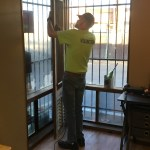 a volunteer fixes a window screen