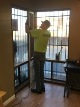 a volunteer fixes a window screen
