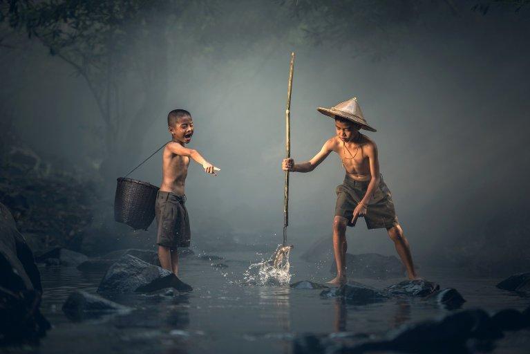 Dos niños pescando en un riachuelo.