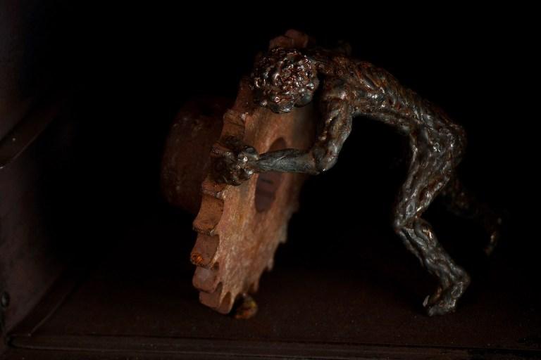 Fondo negro: escultura de hombre moviendo una rueda pesada