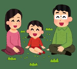 女の子を中心にして話をしている芝生に座っている家族連れのイラスト
