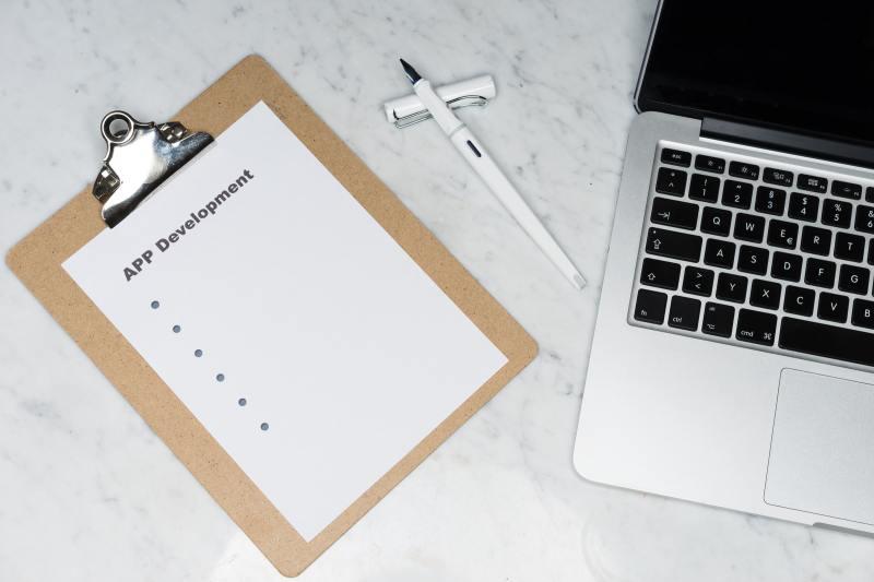 A photo of a clipboard and a Macbook depicting successful app development