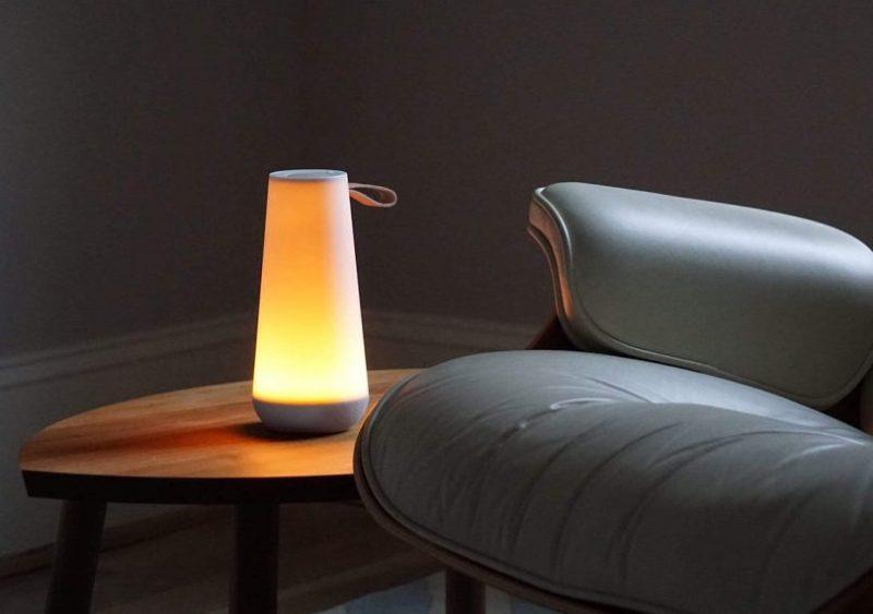 Pablo Designs UMA Mini Light and Speaker on a side table illuminating a dark room