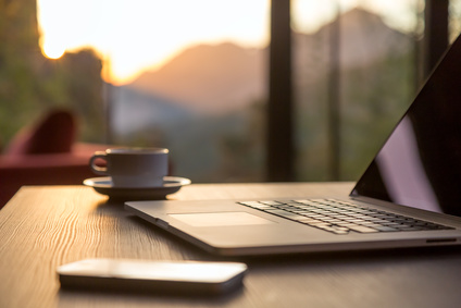 Nomad work Concept Image Computer Coffee Mug and Telephone large windows and sun rising, focus on laptop touchpad