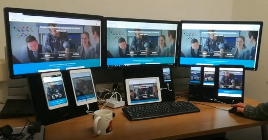 desk with a lot of devices to test a website on various devices and browsers - same website page is seen on mobiles, tablets and bigger screens