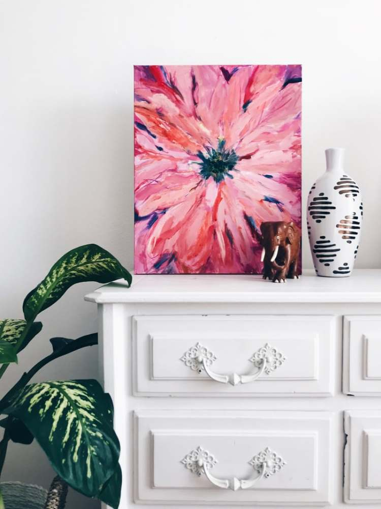 Seasonal decor changes demonstrated with a bright floral picture leaning on white dresser.