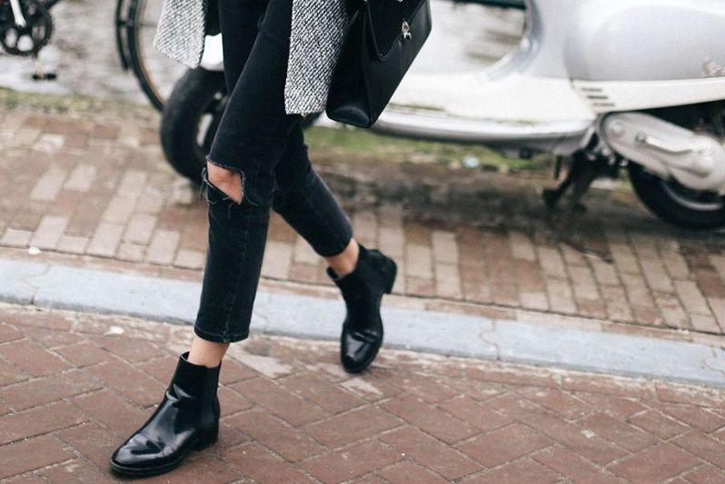 Lesklé kožené boty při chůzi na ulici, roztrhané džíny skútr