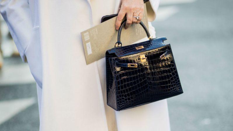 černá kožená kabelka s hadím motivem, ženská ruka s prstýnkem