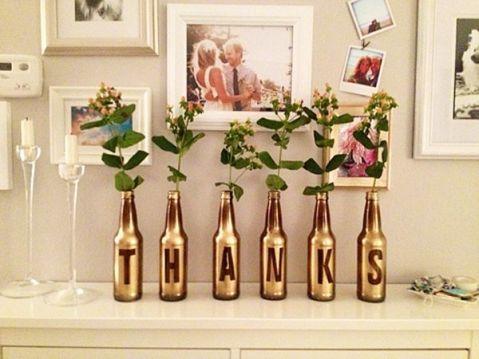 Garrafas de vidro pintadas em dourado, servindo de vasos de flores na decoração