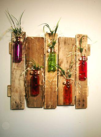 Vidros fazendo o papel de vasos em mural de pallets na parede