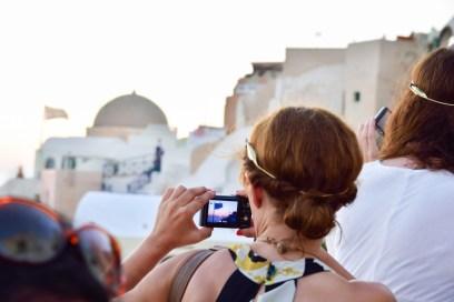 Woman taking photos with camera in Oia Santorini