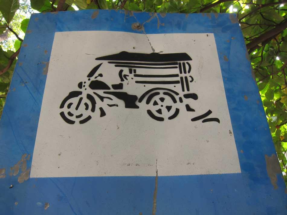 Panneau de signalisation routière avec un tuk tuk dessiné au pochoir