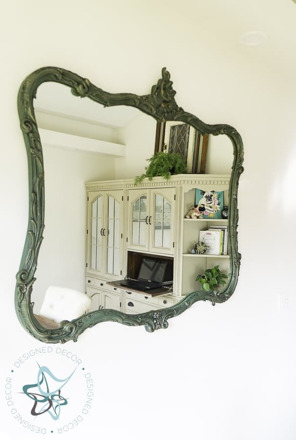 antique painted mirror with reflection of office shelves
