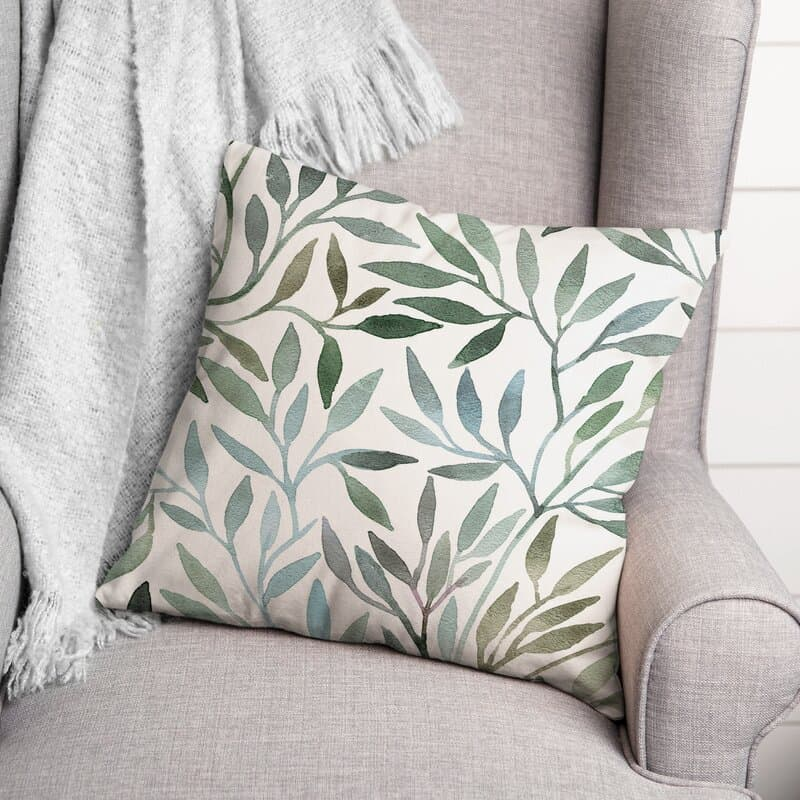 green leaves print pillow sitting on a chair