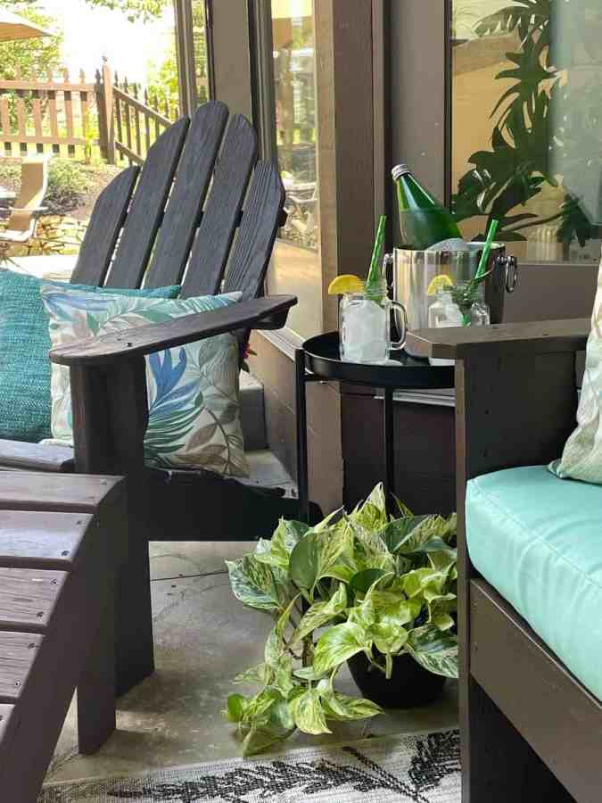 image of an Adirondack with decorative outdoor pillows and a side table with drinks