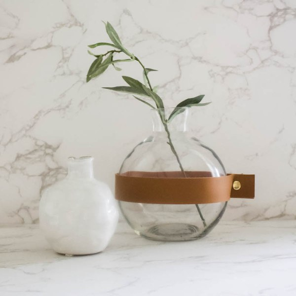 SHOP NOW - This glass vase with leather cuff and brass details make it perfect for fall. Great for a coffee table or bookshelf.  Designed Simple