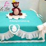 Turquoise Fondant Cake with White Frills and Ribbons with Bear with a Crown.