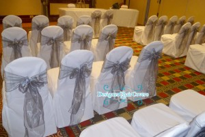 Wedding chair covers with a silver organza sash
