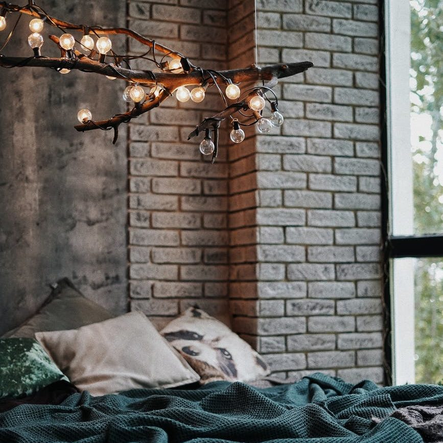 glowing lights on branch in air over bed in room