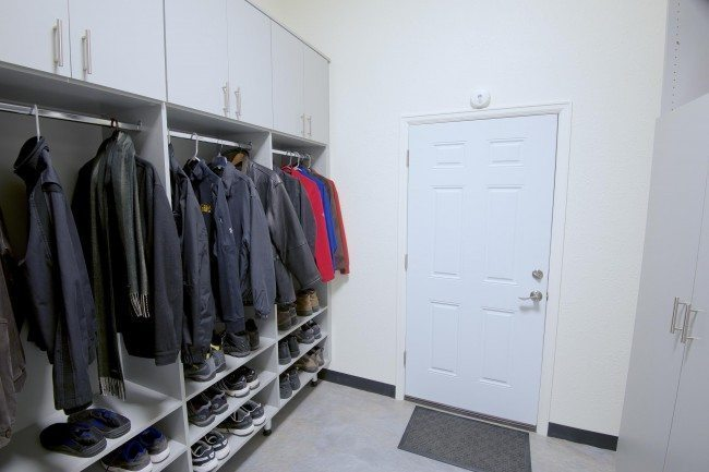 In the mud room design, Polly designed custom-builtstorage areasin a light-grey melamine with long bar handles to store extra coats and shoes as well as bins for hats, gloves, and scarves, thus freeing space in the hall and master closets. Closed shelving and drawers were installed in the mudroom for brooms, mops and cleaning supplies, which maximized and increased the useable space in the laundry room.