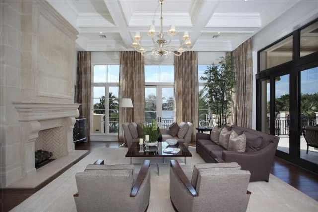 Şömine süslemeli tavan ve avizeli köşe düzenine sahip lüks oturma odası
