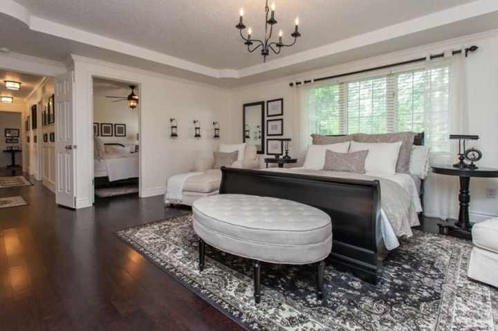 Large Master Bedroom Layout With Lounge Furniture Sleigh Bed And Round Plush Ottoman