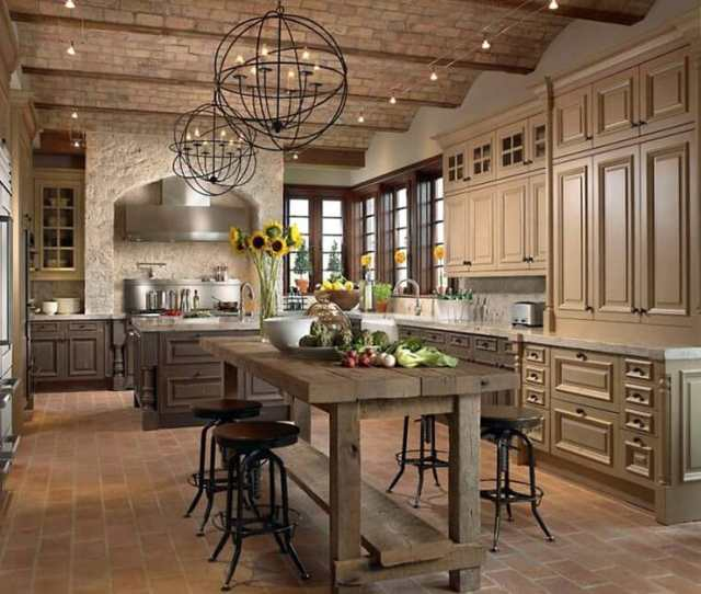 French Country Kitchen With Wood Tone Cabinets Globe Pendant Lights And Rustic Wood Table