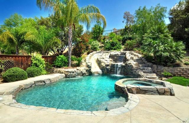 Kaya kaydırağı ve yüksek jakuzili serbest biçimli yüzme havuzu