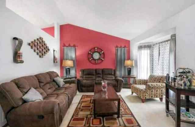 Kahverengi mobilya kırmızı vurgulu duvarlar ile oturma odası