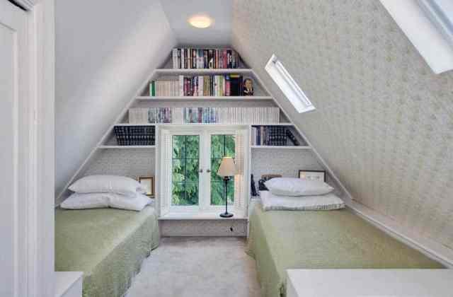 Yerleşik kitap rafları ve yatakların altında yatak odası bulunan tavan arası misafir odası
