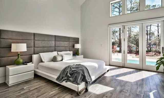 Parke döşeme büyük yatak başlığına sahip ebeveyn yatak odası