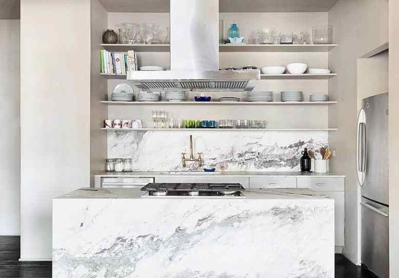 Contemporary kitchen with white cabinets quartz waterfall island and open shelving with glassware dishes