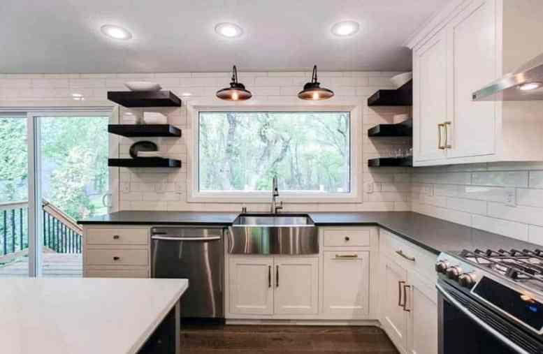 Keuken met zwarte open rekken lange metrotegel en witte kasten