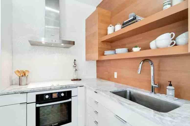 Kleine moderne keuken met open houten planken en witte onderkasten