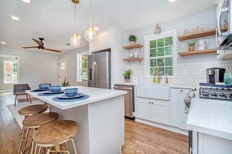 Witte keuken open planken tegel backsplash en eeteiland met barkrukken