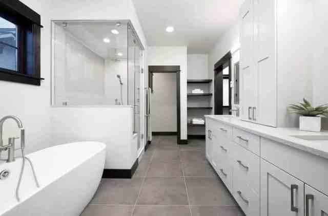 Buharlı duş ve koyu ahşap pencere kapı çerçeveleri ile beyaz makyaj masası içeren ana banyo