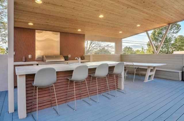Beton tezgahlı açık mutfak, oluklu yan ada ve kapalı veranda
