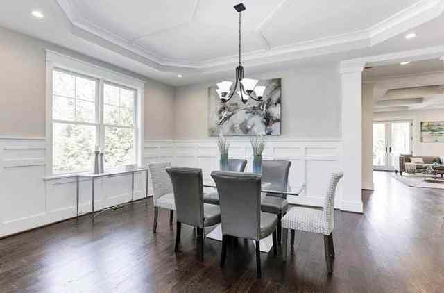 Masa orta süsleri, tepsi tavanı ve beyaz lambri ile çağdaş yemek odası
