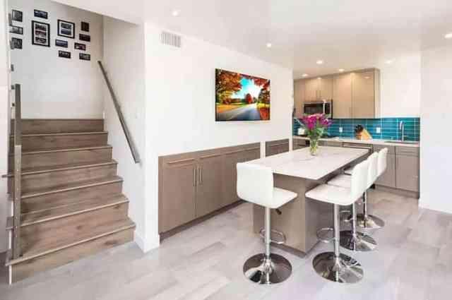 Gömme duvar dolabı deposu ve bar tabureli ada ile modern bodrum mutfak
