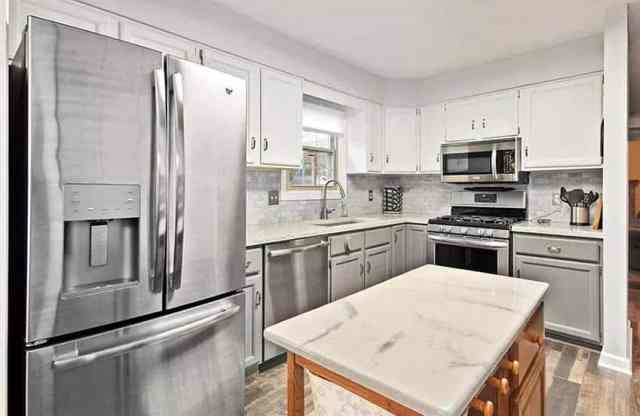 Epoksi tezgahlı mutfak, beyaz dolaplar, paslanmaz çelik aletler ve ahşap zeminler
