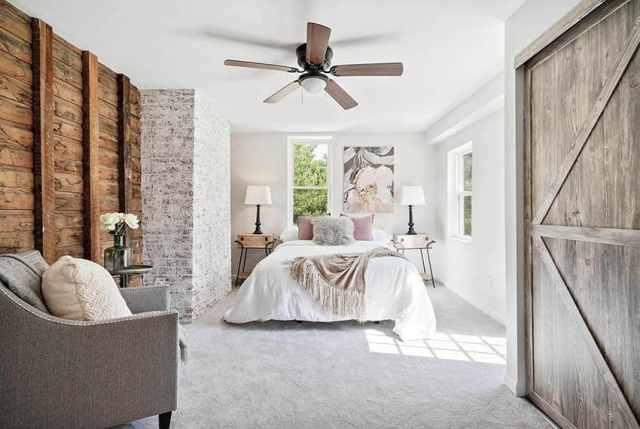 Geri kazanılmış ahşap vurgulu duvar beyaz badanalı tuğla sürgülü ahır kapısı ile modern çiftlik evi yatak odası