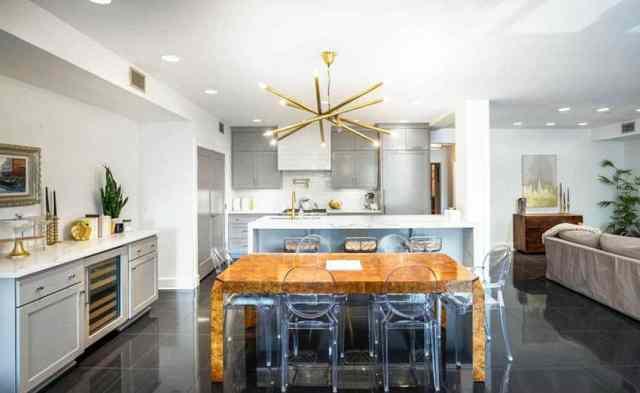 Gri dolaplı şefler mutfağı beyaz kuvars tezgahları şarap dolabı yemek adası ve ahşap masa