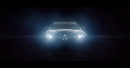 A Mercedes-Benz shines its lights in complete darkness.