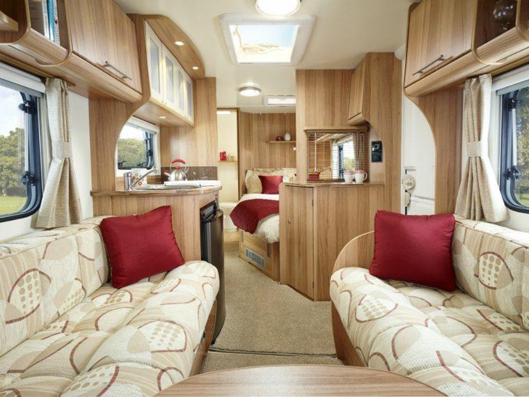 interieur de caravane amenage avec deux canapes un coin cuisine et un grand lit