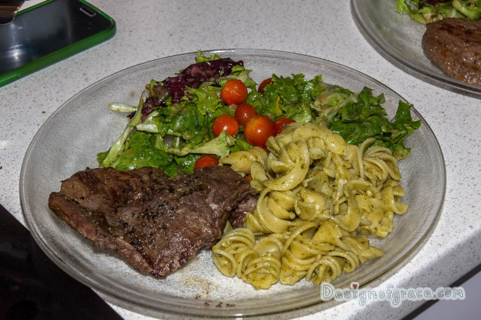 a plate of food with a kangaroo steak on the left which has been nicely browned with pesto pasta on the right and the home grown green and red lettuce and cherry tomatoes on top of the plate