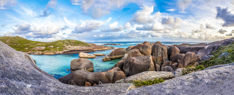 Rocks which look like elephants on the right. With cloudy blue skies and water in the middle