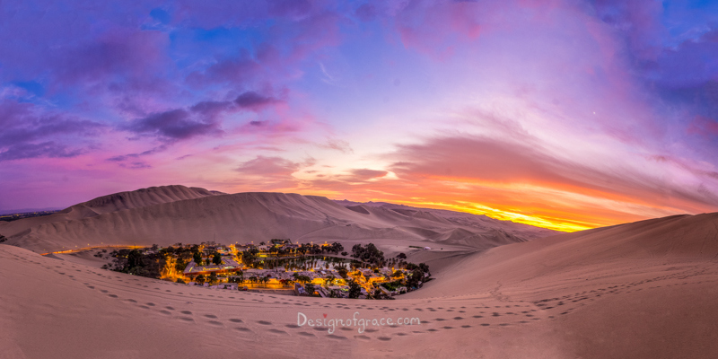 Blue, orange and purple skiles at sunset with the city of huacachina with lights lit up