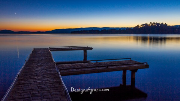 Still waters at Flathead Lake Jetty at sunset with orange and blue colours