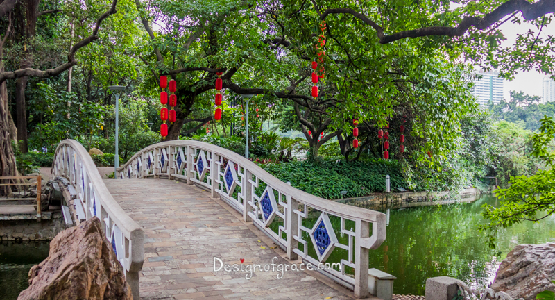 Liwan Lake Park bridge with green trees and red lanterns hanging from the trees with the lake on the right, Guangzhou, China